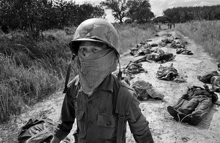In this Nov. 27, 1965 photo, a Vietnamese litter bearer wears a face mask to keep out the smell as he passes the bodies of U.S. and Vietnamese soldiers killed in fighting against the Viet Cong at the Michelin rubber plantation, about 45 miles northeast of Saigon. (Photo by AP Photo/Horst Faas, File)