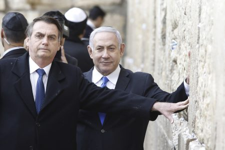 Brazilian President Jair Bolsonaro (L) and Israeli Prime Minister Benjamin Netanyahu touch the Western wall, the holiest site where Jews can pray, in the Old City of  Jerusalem on April 1, 2019. - Bolsonaro arrived in Israel just ahead of the country's polls in which his ally Prime Minister Benjamin Netanyahu faces a tough re-election fight. (Photo by Menahem KAHANA / POOL / AFP)
